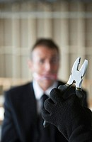 Hand holding a plier with gagged businessman looking at it