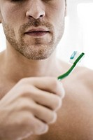 Man holding toothbrush with toothpaste (thumbnail)