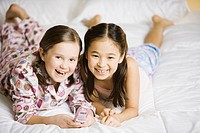 Portrait of two girls holding cell phone on bed