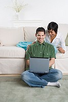 Hispanic couple looking at laptop