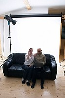 young woman and young man sitting on a couch in photo studio
