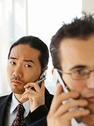 Two young businessmen using mobile telephones, close-up