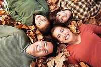 Hispanic family laying in autumn leaves