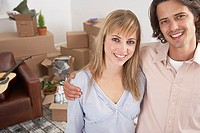 Man and woman in home with cardboard boxes and guitar smiling