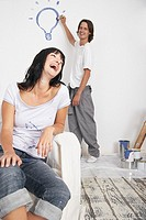 Man painting light bulb on wall and woman on sofa