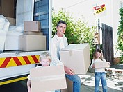 Man with boy and girl carrying boxes with moving van outdoors