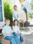 Man with boy and girl outdoors with boxes and sold sign on house