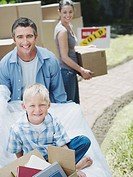Boy sitting with books in box outdoors with man and woman carrying cardboard box with sold sign in yard