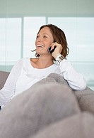 Woman talking on cell phone on sofa smiling (thumbnail)