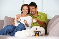 Man and woman watching television eating ice cream