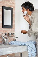 Man in robe shaving