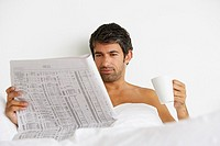 Man lying down in bed reading