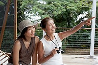 Asian mother and adult daughter pointing and looking