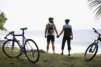 Cyclist couple holding hands on cliff over ocean