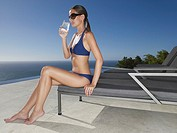 Woman in bikini and sunglasses with cold beverage outdoors