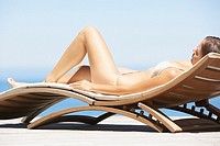Woman in bikini lying down on folding chair outdoors