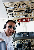 Asian male pilot smiling in cockpit of airplane