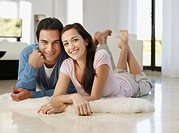 Smiling couple lying on floor at home