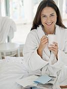 Woman in bathrobe sitting on bed enjoying a cup of coffee