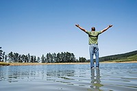 Man standing on water with arms up