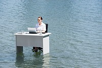 Businesswoman sitting at desk in water with laptop