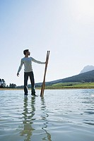 Man standing on water with oars