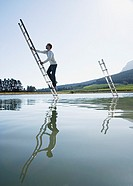 Man climbing ladder in water