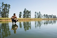 Man crouching on water with trees