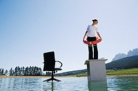 Businesswoman standing on desk on water with flotation device