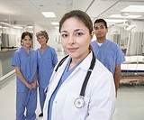 Hispanic female doctor with nurses in background (thumbnail)