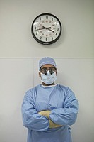 Male surgeon standing under wall clock