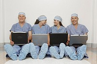 Row of doctors sitting on floor with laptops