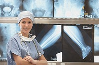 Hispanic female doctor smiling in front of x-rays on lightbox