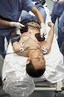 Asian patient being defibrillated in emergency room