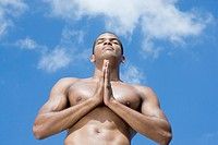 Bare-chested African man meditating