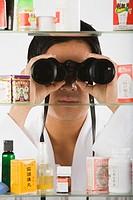 Asian man looking through binoculars at medicine cabinet