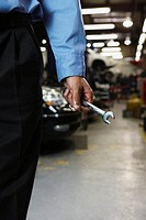 Male auto mechanic holding wrench