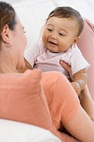 Hispanic baby smiling at mother