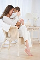 Hispanic mother sitting in chair hugging baby