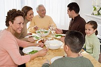 Multi-generational Hispanic family eating at Thanksgiving table