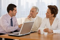 Hispanic businessman talking to senior couple in home