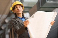 Hispanic businesswoman in hard hat holding blueprints