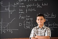 Hispanic boy smiling in front of math formula on blackboard