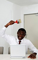 Businessman holding a paint brush while using laptop