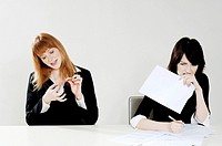 Businesswoman shaping her fingernail while her colleague is busy doing her work