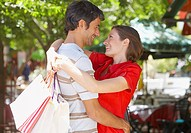 Woman with shopping bags embracing man