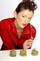 Woman holding a fork with coloured pasta on the table