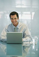 Businessman with laptop and glass of water smiling