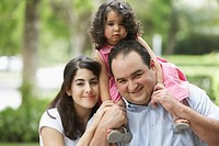 Hispanic father and mother with daughter on shoulders
