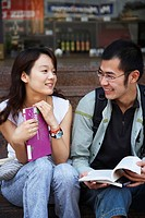 Young Asian couple holding school books